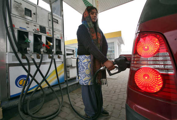 A woman fills a vehicle with petrol at a fuel station in Jammu.