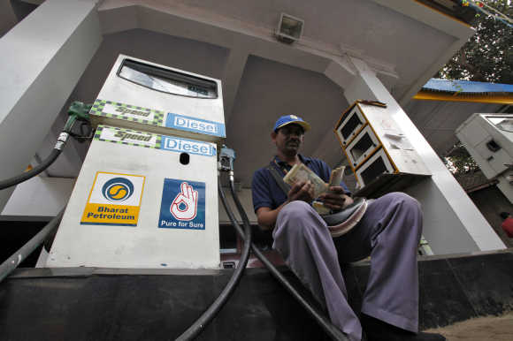 A worker counts cash at a fuel station in Mumbai.