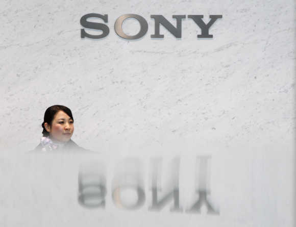 A receptionist of Sony Corp is pictured under the company's logo in Tokyo.