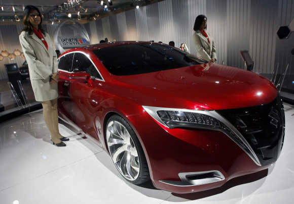 Models stand next to Maruti-Suzuki's 'Kizashi' concept car during the 9th Auto Expo in New Delhi.