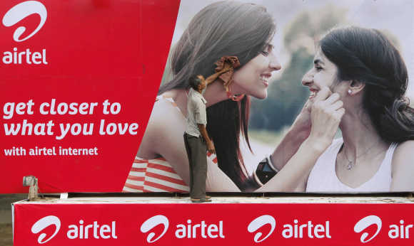 A labourer cleans a Bharti Airtel advertisement billboard installed on a truck in Kolkata.