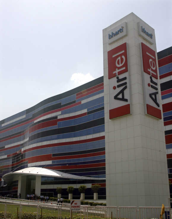 Employees of Bharti Airtel walk in front of their office on the outskirts of New Delhi.