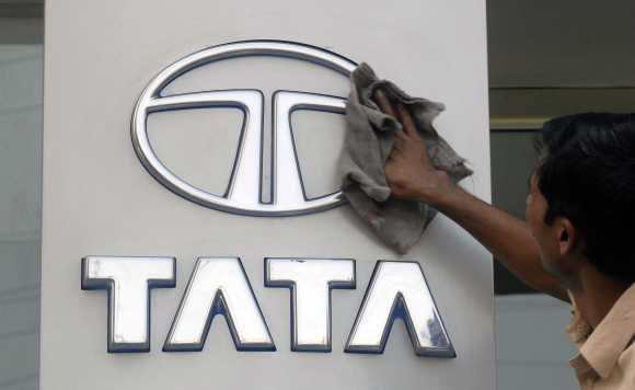 A worker cleans a Tata Motors logo in Hyderabad.