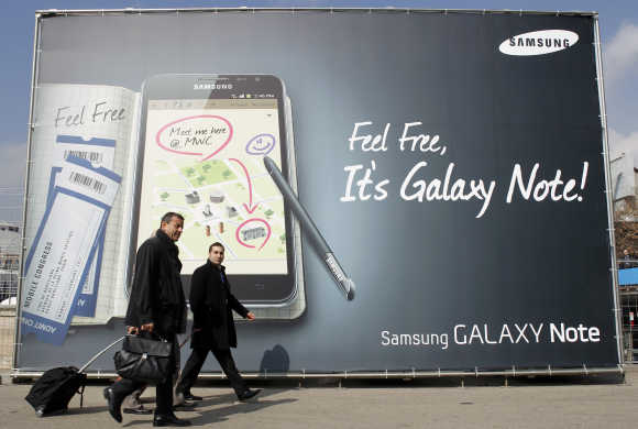 Visitors walks past a Samsung Galaxy tablet advertisement during the Mobile World Congress in Barcelona.