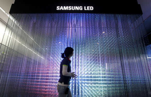 An employee of Samsung Electronics walks past LED lighting drums displayed for visitors at a showroom in Seoul.