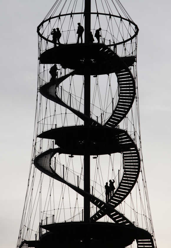 People walk on a lookout tower during sunset in a park in Stuttgart.