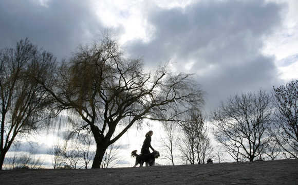 Woman walks with her dog on a dyke along the Weser river in Bremen.
