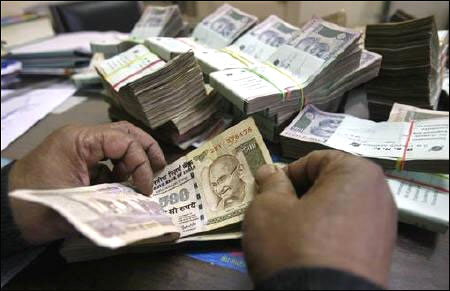 An employee counts rupee notes at a cash counter.
