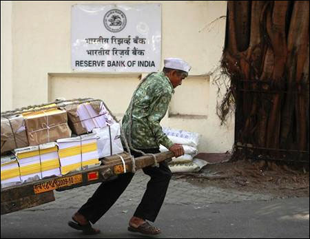 A man pulls a hand-drawn cart in front of the Reserve Bank of India building in Mumbai.