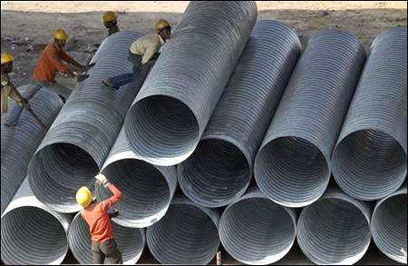 Labourers work on steel pipes.