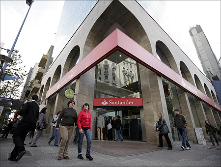 Residents walk infront of Santander branch in downtown Montevideo.