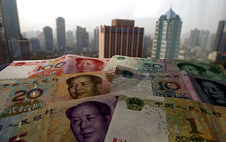 Different values of China's yuan banknotes are placed on a window sill as Shanghai's skyscrapers are seen in the background, in this photo illustration taken in Shanghai.