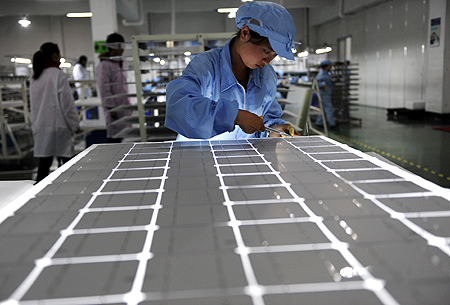 An employee works on a solar panel production line at a solar company workshop in Yongkang, Zhejiang province.