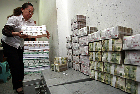 An employee arranges bundles of Renminbi banknotes at a bank in Suining, Sichuan province.