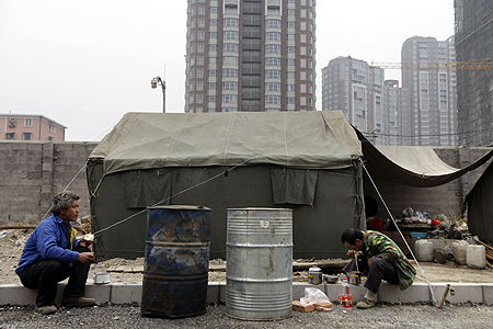 Labouers eat their lunch outside residential construction site in Beijing.