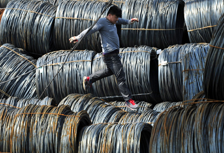 A labourer walks on coils of steel wire at a steel market in Shenyang, Liaoning province.