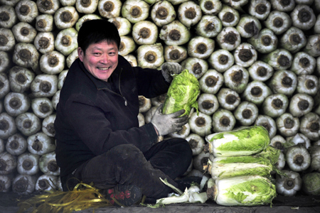 vendor smiles as he waits for customers in front of piles of Chinese cabbage at a vegetable wholesale market in Shenyang, Liaoning province.