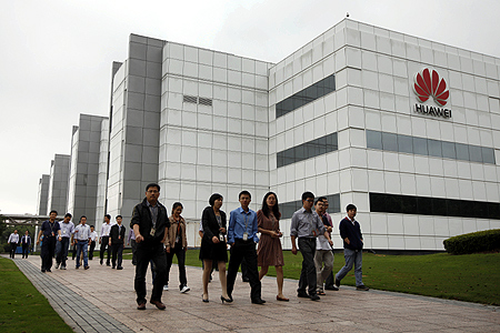 Employees of Huawei Technologies Co. Ltd. walk past the company office in Shenzhen, Guangdong province.