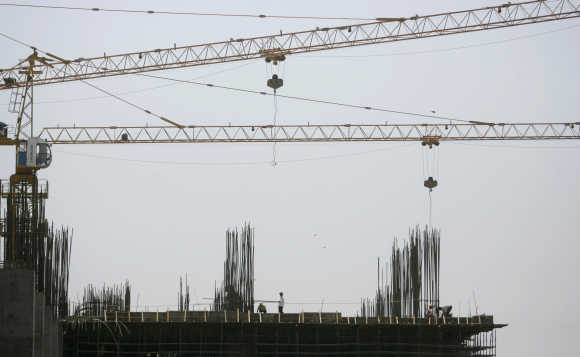 Workers stand on top of a building under construction in Mumbai.