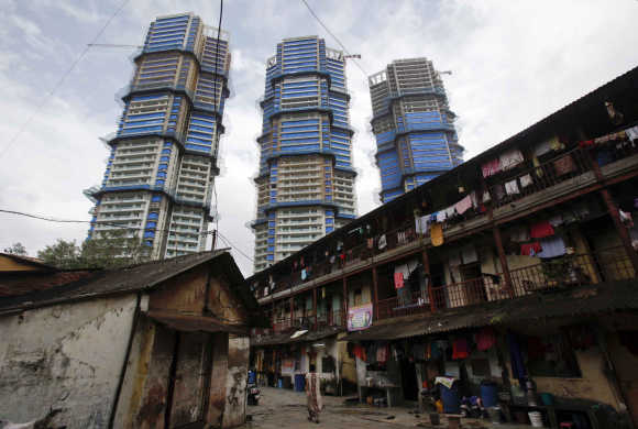High-rise residential towers under construction are pictured behind an old residential building in Mumbai.