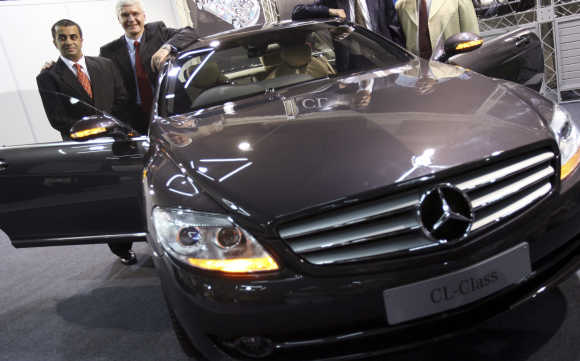 Wilfried Aulbur, second left, Managing Director and Chief Executive Officer of Daimler Chrysler India, and car dealer Mohan Mariwala pose next to Mercedes-Benz CL class car in Mumbai.