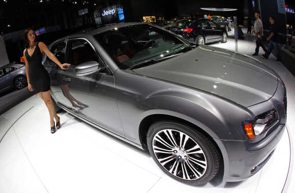 Model next to Chrysler 300 S on display at New York International Auto Show.