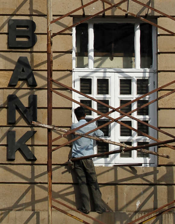 A worker stands on scaffoldings at the headquarters of Central Bank of India in Mumbai.