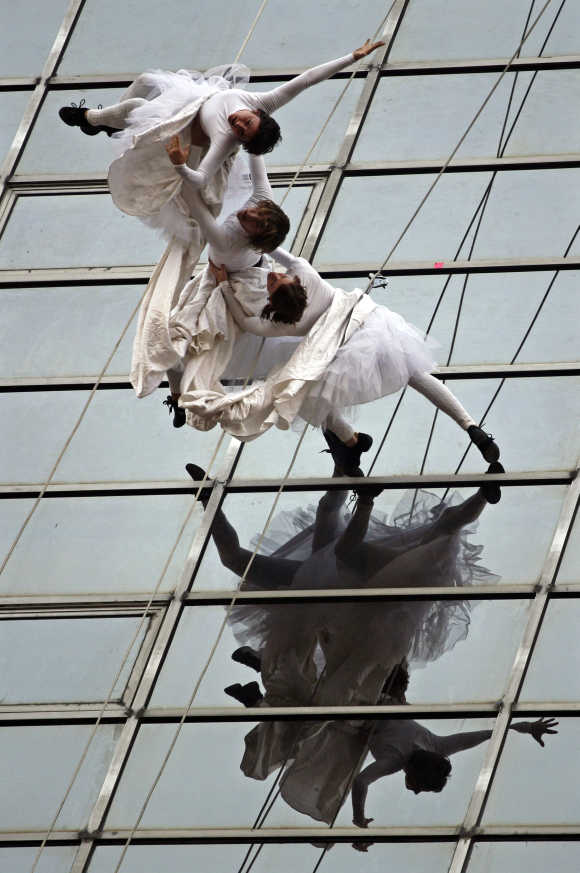 Artists of Project Bandaloop from the US perform an aerial dance on the side of the building of an insurance company in New Delhi.