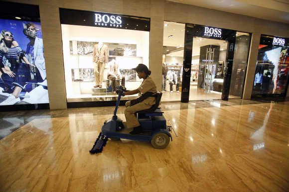 An employee operates a floor cleaning machine in front of a Hugo Boss showroom inside a shopping mall in Mumbai.