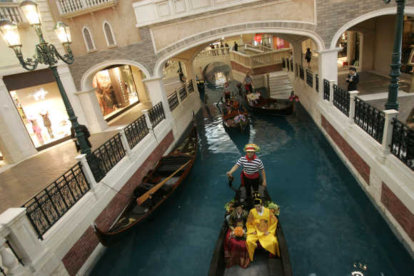 Newlywed couples from South Korea, Malaysia and Thailand sit on gondolas before the opening ceremony of the Venetian in Macau.