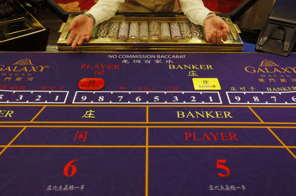 A croupier sits in front of a gaming table inside a casino on the opening day of Galaxy Macau.