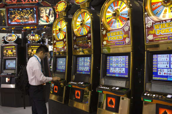 A man plays slot machines during the Global Gaming Expo Asia in Macau.
