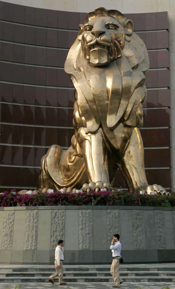 People walk past a giant lion sculpture at the MGM Grand Macau hotel resort in Macau.