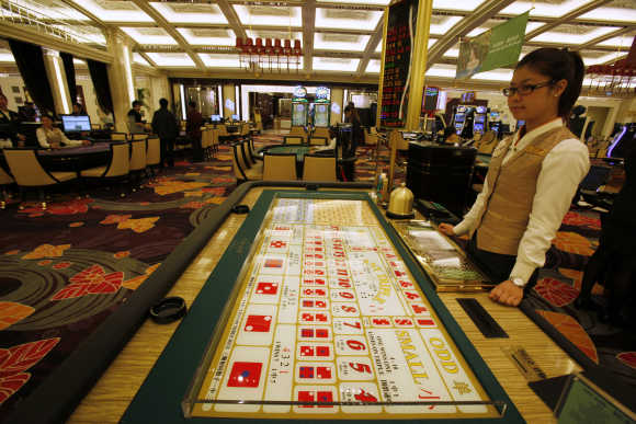 A croupier stands in front of a gaming table inside a casino on the opening day of Galaxy Macau.