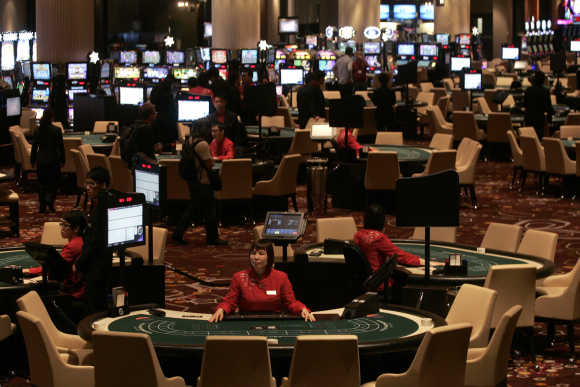 Dealers wait for customers at the casino inside Melco Crown Entertainment's latest gaming resort City of Dreams in Macau.