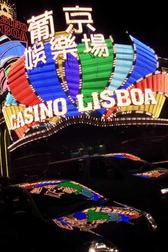 Lights from the Casino Lisboa are reflected on vehicles in Macau.