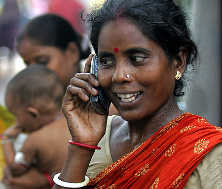 Tulsi Prasad, an Indian slum dweller, uses a mobile phone in Kolkata.