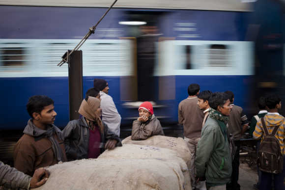 Workers wait to cross tracks as a train to passes nearby to the Nizamuddin Railway Station.