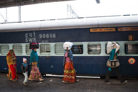 Families alight from a train at the Nizamuddin Railway Station.