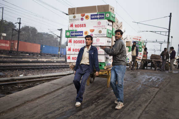 Workers move the morning delivery of flowers from a train at the Nizamuddin Railway Station.