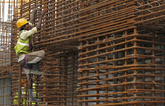 A worker climbs to fasten iron rods together at the construction site in Mumbai. Photo is for representation purpose only.