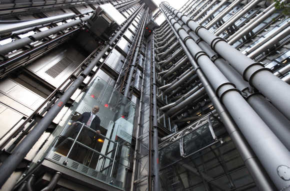 Architect Richard Rogers poses inside an elevator in the Lloyd's building in London. Rogers, who designed the building for the insurance company, was marking its 25th anniversary.