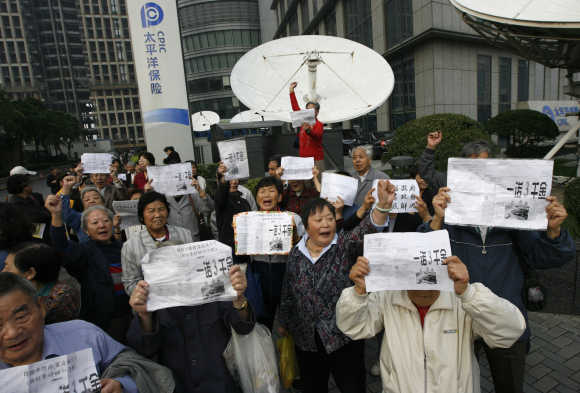 People protest in front of the China Pacific Insurance Company building in Shanghai.