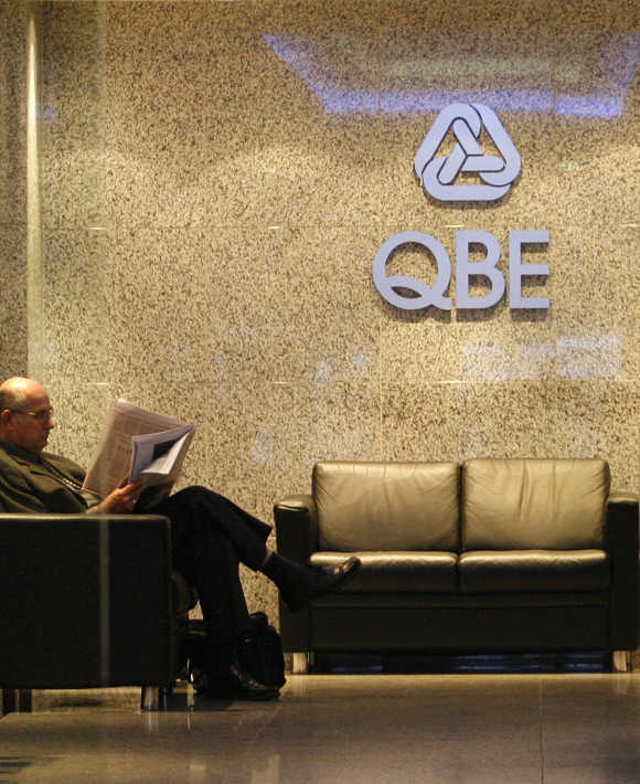 A Man Reads The Newspaper At The QBE Insurance Group Headquarters In  Central Sydney.