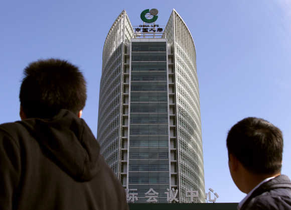 Pedestrians look up towards the headquarters of China's largest life insurance company, Ch
