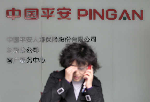 A woman talks on her mobile at a customer service centre of Ping An Insurance of China in Beijing.
