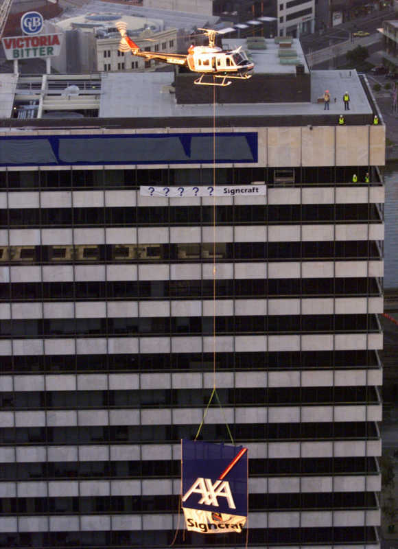 A helicopter lifts a six metres square AXA sign, one of two, weighing 1,500kg attached by a 150-foot-long steel cable to the roof of a building in Melbourne.