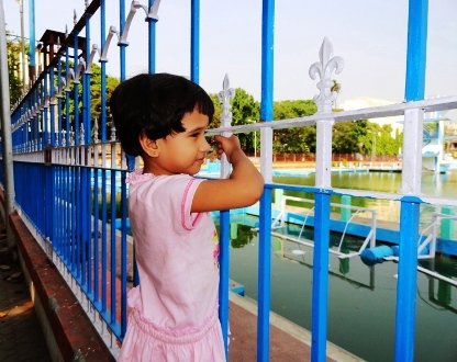 A child peeps through the railings surrounding College Square pool in north Kolkata.