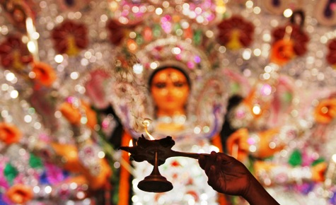 A priest holds a lamp while praying in front of an idol during Durga Puja in Kolkata.