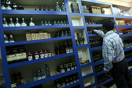 A man holds an alcohol bottle inside a wine shop.